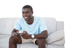 Smiling man sitting on couch playing video games Royalty Free Stock Image
