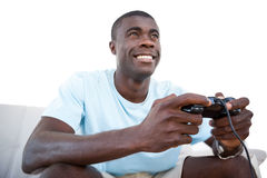 Smiling man sitting on couch playing video games Stock Photography