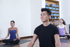 Smiling man sitting cross-legged in a yoga class Royalty Free Stock Photo