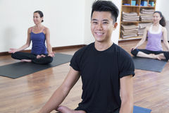 Smiling man sitting cross-legged in a yoga class Royalty Free Stock Photography