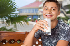 Smiling man sitting and drinking kefir Stock Images