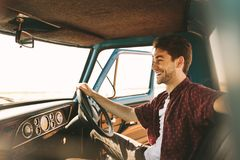 Man on vacation driving his car. Smiling man sitting in the driver seat of an old car. Man sitting in his vintage car holding the steering wheel with the door Stock Photo