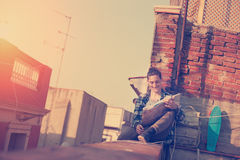 Smiling man sitting on the edge on high roof looking at map, backpack and skateboard. Brave and smiling man sitting on the edge on high roof looking at map Royalty Free Stock Images
