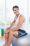 Smiling man sitting on exercise ball Stock Photos