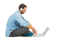 Smiling man sitting on floor using laptop and headphones Royalty Free Stock Photography