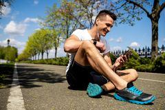 Happy man is exploiting phone after workout. Smiling man is sitting on green road and holding phone while looking at screen. Male is using earphones and Royalty Free Stock Images