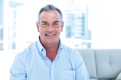 Smiling man sitting at home Stock Photography