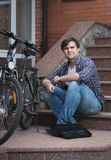 Smiling young man sitting on house porch and repairing bicycle. Smiling man sitting on house porch and repairing bicycle Stock Image