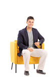 Smiling man sitting on a modern chair Stock Images