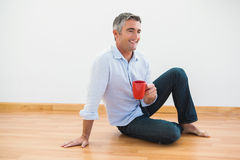 Smiling man sitting with a mug and barefoot Stock Images