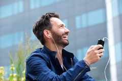 Smiling man sitting outdoors and listening to music. Close up side portrait of smiling man sitting outdoors and listening to music using mobile phone Royalty Free Stock Photography