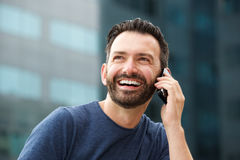 Smiling man sitting outdoors and talking on smart phone. Close up portrait of smiling man sitting outdoors and talking on smart phone Stock Photo