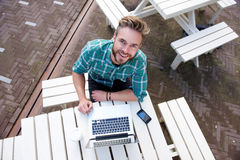 Smiling man sitting outside with laptop from above Stock Photo