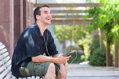 Smiling man sitting outside with mobile phone and headphones Royalty Free Stock Photos