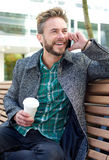 Smiling man sitting outside with mobile phone Stock Image