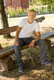 Smiling man sitting on a park bench Stock Photo