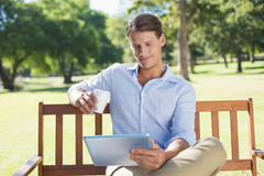 Smiling man sitting on park bench using tablet drinking coffee Stock Photo