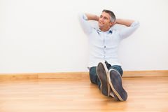 Smiling man sitting on the parquet relaxing Royalty Free Stock Photography