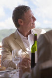 Smiling man sitting at patio table with wine glasses Stock Photos