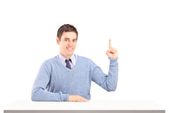 Smiling man sitting and pointing with finger Royalty Free Stock Images