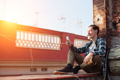 Smiling man sitting on the roof with mobile phone and listening music in earphones. Young and smiling man sitting on the roof with mobile phone and listening Stock Photo