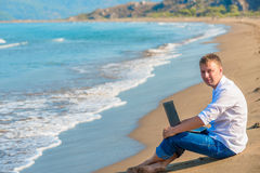 Smiling man sitting on the sand Royalty Free Stock Photography