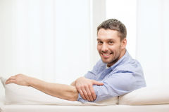 Smiling man sitting on sofa at home. Home and happiness concept - smiling man sitting on sofa at home royalty free stock photo
