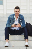 Smiling man sitting on steps with headphones and mobile. Full body portrait of smiling man sitting on steps with headphones and mobile Royalty Free Stock Image