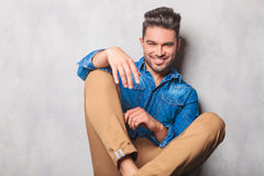 Smiling man sitting in studio background legs crossed posing Royalty Free Stock Photo