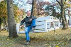 Smiling man is sitting on swing. Autumn. Smiling man is sitting on swing in the autumn park, relaxing and enjoying life. Wonderful morning Stock Image