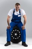 Smiling man sitting on tire on grey background. Royalty Free Stock Photo