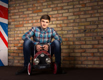 Smiling Man Sitting on Toy Automobile Stock Photography