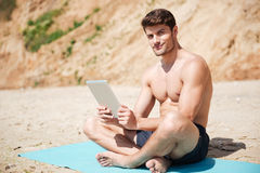 Smiling man sitting and using tablet on the beach Royalty Free Stock Photo