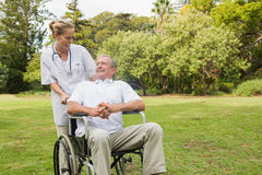 Smiling man sitting in a wheelchair talking with his nurse pushi. Smiling men sitting in a wheelchair talking with his nurse pushing him at the park Royalty Free Stock Images