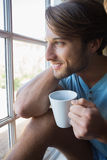 Smiling man sitting by the window having coffee Stock Photos