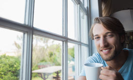 Smiling man sitting by the window having coffee Stock Photography