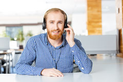 Smiling man sitting on workplace and using headset. Portrait of smiling bearded man sitting on workplace and using headset Stock Image