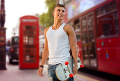 Smiling man with skateboard on london city street. Leisure, summer holidays, sport, travel and people concept - smiling man or teenage boy with skateboard with royalty free stock photography