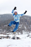 Smiling man in ski sport suit jumps on mountain stock image