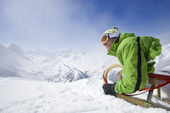 Smiling man with sled on mountain top Stock Image