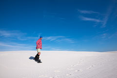 Smiling man slides down on a snowboard on the sand dune stock images