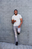Smiling man with smart phone leaning on gray wall Royalty Free Stock Images