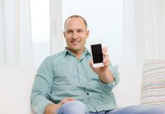 Smiling man with smartphone at home Royalty Free Stock Photos