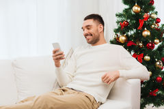 Smiling man with smartphone at home for christmas Royalty Free Stock Photos