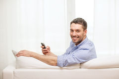 Smiling man with smartphone at home. Home, technology and internet concept - smiling man with smartphone sitting on couch at home royalty free stock image