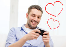 Smiling man with smartphone at home Stock Images