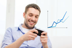Smiling man with smartphone at home. Home, technology and internet concept - smiling man with smartphone sitting on couch at home stock photos