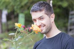Smiling man smelling a rose Stock Images