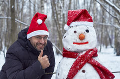 Smiling man with a snowman Stock Images