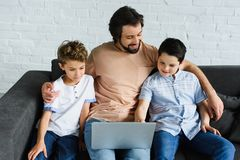 Smiling man and sons near by using laptop on sofa. At home stock photos